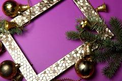 Fundo Em uma superfície roxa brilhante é um quadro da foto do ouro, decorado com ramos do abeto e brinquedos do Natal imagem de stock royalty free