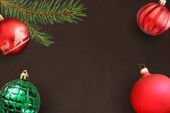 Fundo escuro com ramo do abeto do Natal, a bola com nervuras maçante e verde ondulada vermelha Imagem de Stock