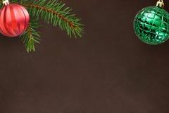 Fundo escuro com ramo do abeto do Natal, a bola com nervuras ondulada e verde vermelha Fotos de Stock Royalty Free