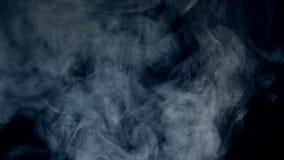 Fundo escuro e sopros da névoa que flutuam e que dissolvem-se filme