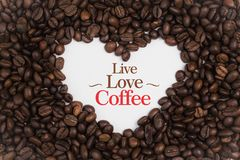 Fundo feito de feijões de café em uma forma do coração com ` de Live Love Coffee do ` da mensagem Imagens de Stock Royalty Free