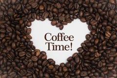 Fundo feito de feijões de café em uma forma do coração com tempo do café do ` da mensagem! ` Imagens de Stock