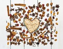 Fundo feito de vários tipos de especiarias Centralmente na bacia da argila do quadro na forma de um coração Fotos de Stock