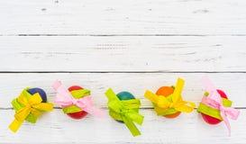 Fundo feliz da Páscoa com a decoração colorida dos ovos na madeira branca Fotografia de Stock Royalty Free