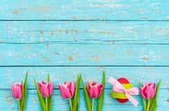 Fundo feliz da Páscoa com tulipas e o ovo cor-de-rosa Fotografia de Stock Royalty Free