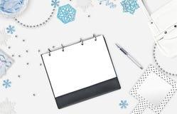 Fundo feminino do Natal com lugar para o texto Flocos de neve azuis, grânulos brilhantes, caderno e pena no fundo branco Plano pa Fotografia de Stock Royalty Free