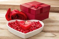 Fundo festivo ao dia de Valentim A flor aumentou, caixa de presente, uma placa coração-dada forma e uma vela dada forma coração fotografia de stock