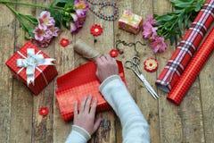 Fundo festivo A composição da vista superior das mãos da mulher envolve o presente para o aniversário, dia do ` s da mãe, dia do  Fotografia de Stock Royalty Free