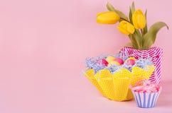 Fundo festivo da Páscoa - amarelo, ovos azuis, vermelhos na cesta amarela, tulipas, queque no fundo do rosa pastel com espaço da  fotografia de stock