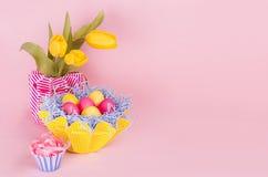 Fundo festivo de easter da primavera - ovos coloridos pintados caseiros, ramalhete das tulipas na luz pastel - fundo cor-de-rosa Imagens de Stock Royalty Free