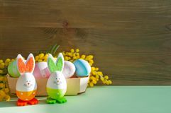 Fundo festivo de Easter Os coelhinhos da Páscoa e os ovos da páscoa na caixa perto da mimosa florescem Fotografia de Stock Royalty Free