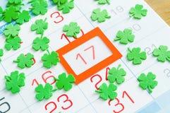 Fundo festivo do dia do ` s de St Patrick Os quatrefoils verdes que cobrem o calendário com a laranja moldaram o 17 de março imagens de stock royalty free