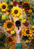 Fundo floral do verão Uma caneca de café em uma mão do ` s da mulher em um fundo de madeira com girassóis e wildflowers Fotografia de Stock Royalty Free
