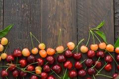 Fundo fresco doce das cerejas Cerejas dispersadas no teste padrão de madeira rústico azul com espaço da cópia Backround do fruto  imagens de stock
