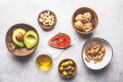 Fundo gordo saudável do alimento Peixes, porcas, óleo, azeitonas, abacate no fundo branco, vista superior imagens de stock