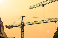 Fundo industrial abstrato com as silhuetas dos guindastes de construção sobre o céu do por do sol Fotografia de Stock Royalty Free