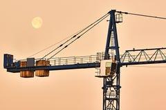 Fundo industrial abstrato com as silhuetas dos guindastes de construção sobre o céu do por do sol Foto de Stock Royalty Free