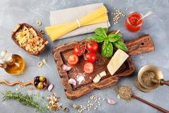 Fundo italiano com tomates da videira, manjericão do alimento, espaguete, azeitonas, Parmesão, azeite, alho foto de stock