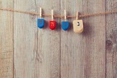 Fundo judaico do Hanukkah do feriado com a parte superior de giro de madeira do dreidel que pendura na corda imagens de stock