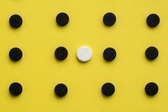Fundo médico conceptual com as cápsulas pretas do carvão vegetal ativado com um comprimido branco em um fundo amarelo alto imagem de stock