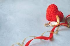 Fundo mínimo do dia de Valentim Coração da linha, relógio de bolso do ouro e fitas vermelhos no fundo cinzento do cimento Hora de imagem de stock royalty free