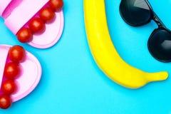 Fundo mínimo do verão criativo com óculos de sol, a banana plástica e as sandálias Conceito liso da configuração fotos de stock