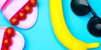 Fundo mínimo do verão criativo com óculos de sol, a banana plástica e as sandálias Conceito liso da configuração imagens de stock royalty free