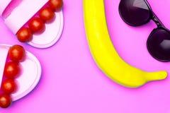 Fundo mínimo do verão criativo com óculos de sol, a banana plástica e as sandálias Conceito liso da configuração fotos de stock royalty free