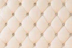 Fundo macio bege do teste padrão da tapeçaria com os botões simétricos nos cantos dos diamantes Mobília macia e cara Fotos de Stock
