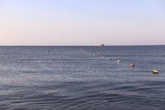 Fundo Mar azul, céu cor-de-rosa no alvorecer e um navio branco no horizonte foto de stock