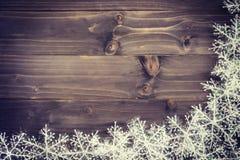 Fundo marrom de madeira do Natal e flocos de neve brancos com spac Imagens de Stock
