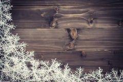 Fundo marrom de madeira do Natal e flocos de neve brancos com spac Imagem de Stock