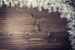 Fundo marrom de madeira do Natal e flocos de neve brancos com spac Fotografia de Stock Royalty Free