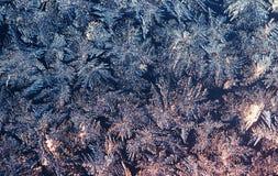 Fundo natural do Natal com um teste padrão gelado no vidro do inverno iluminado pela luz solar fotos de stock