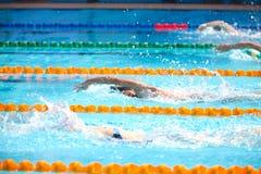 Fundo obscuro da água da gota do respingo na raça da natação com swi Foto de Stock Royalty Free