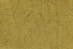 Fundo ondulado amarelo escuro de um material de matéria têxtil Tela com o close up da textura da dobra imagem de stock royalty free