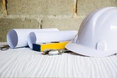Fundo para o arquiteto e a ferramenta do artesão com papel e capacete na parede branca da tabela e do cimento do fundo Fotografia de Stock Royalty Free