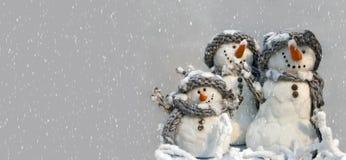 Fundo para o cartão do xmas de um grupo de três bonecos de neve Fotografia de Stock Royalty Free