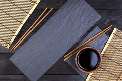 Fundo para o sushi Esteira de bambu, molho de soja, hashis na tabela escura Fotografia de Stock