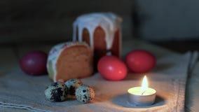 Fundo para um cartão: a vela ardente da luz do close up, ovos da páscoa coloridos no fundo e no bolo da Páscoa cortou em dois pi video estoque