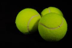 Fundo preto 3 das bolas de tênis fotografia de stock