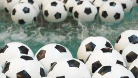 Fundo preto e branco de muitas bolas de futebol Bolas do futebol que nadam em uma água pura video estoque