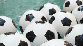 Fundo preto e branco de muitas bolas de futebol Bolas do futebol que nadam em uma água pura vídeos de arquivo