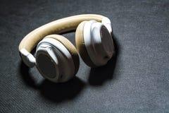 Fundo preto Fones de ouvido grandes para escutar da música Cor branca e bege pele Tecnologias modernas Equipamento portátil imagem de stock royalty free