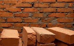 Fundo que consiste em uma parede de tijolo e em diversos tijolos no primeiro plano Fotos de Stock