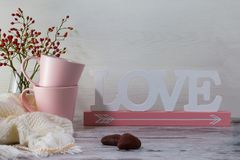 Fundo romântico do dia de Valentim Dois copos cor-de-rosa para o chá e a palavra amam no fundo claro imagem de stock