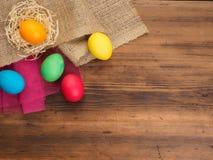 Fundo rural do eco com o ovo e palha coloridos da galinha no fundo da serapilheira e de pranchas de madeira velhas A vista de Fotos de Stock