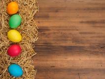 Fundo rural do eco com os ovos e palha coloridos da galinha no fundo de pranchas de madeira velhas A vista da parte superior Fotos de Stock Royalty Free