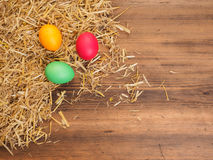 Fundo rural do eco com os ovos e palha coloridos da galinha no fundo de pranchas de madeira velhas A vista da parte superior Imagens de Stock