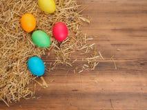 Fundo rural do eco com os ovos e palha coloridos da galinha no fundo de pranchas de madeira velhas A vista da parte superior Foto de Stock Royalty Free